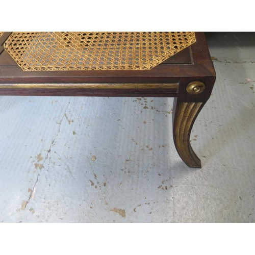 15 - A mahogany and gilt bergere stool in the Regency style, 39cm tall x 100cm x 66cm top