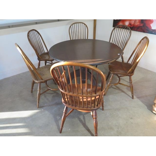 16 - An oak tripod kitchen table with six ash and oak hoop back chairs, 74cm tall x 121cm diameter