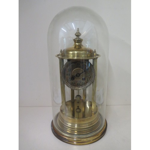 A brass portico clock under a glass dome striking on a bell in running order, some small dents to base but dome good, 45cm tall x 22cm wide