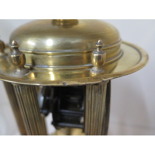 A brass portico clock under a glass dome striking on a bell in running order, some small dents to ba...