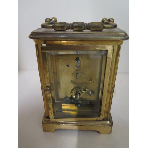 152 - A brass carriage clock, 12cm tall, running, dial good, one small chip to glass door...