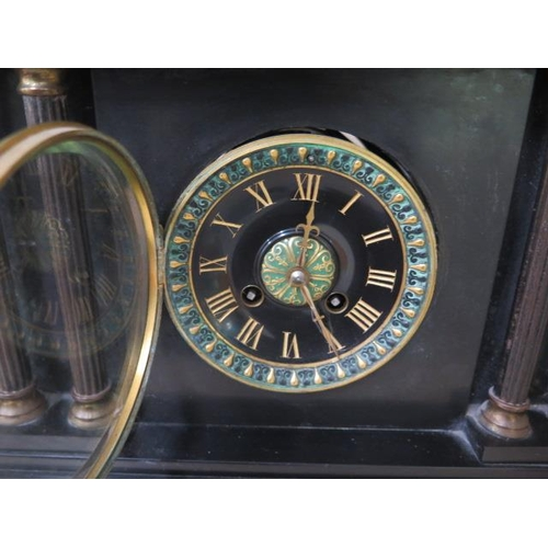 153 - A Victorian black slate striking mantle clock in running order, chip to one corner otherwise general...
