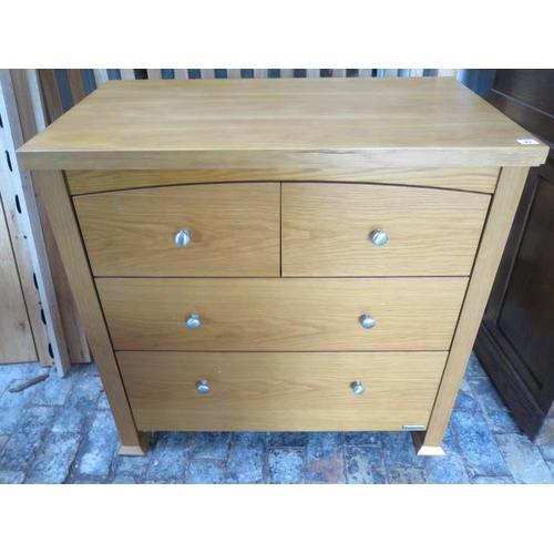 23 - An oak effect four drawer chest by Izziwotnot, 90cm tall x 93cm x 54cm,...