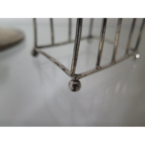 508 - Two small silver toast racks, one with a broken joint, approx 2.9 troy oz and a silver capstan inkwe...