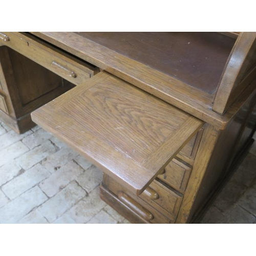 57 - An oak roll top desk with a fitted interior over eight drawers and two slides, 104cm tall x 153cm wi...