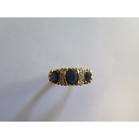 A hallmarked 18ct yellow gold  sapphire and diamond ring, size R, approx 8.3 grams, the central sapphire approx 6mm x 5mm x 2.5mm, in good condition minor abrasions to sapphires