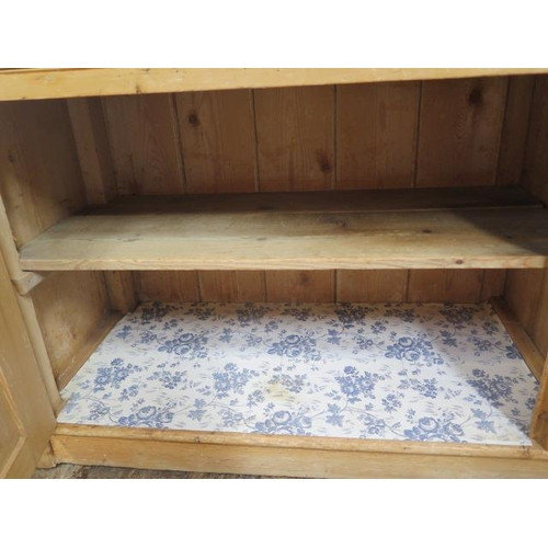 60 - A 19th century stripped pine dresser with an open rack top above three drawers and two cupboard door...