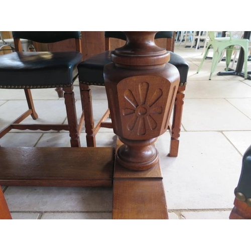 66 - An oak refectory table on carved bulbous supports with 8 green leather upholstered chairs, 76cm tall...