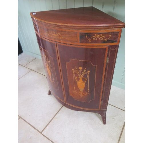 67 - An Edwardian inlaid mahogany bow fronted corner cupboard with two urn inlaid doors on splayed front ...