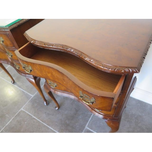 56 - A pair of burr walnut serpentine bedside three drawer chests on cabriole legs both with glass protec...