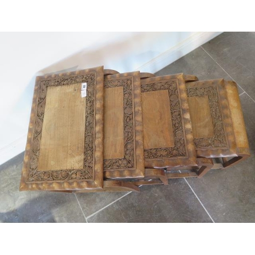 65 - A nest of four carved hardwood Eastern side tables, 52cm tall x 51cm x 41cm