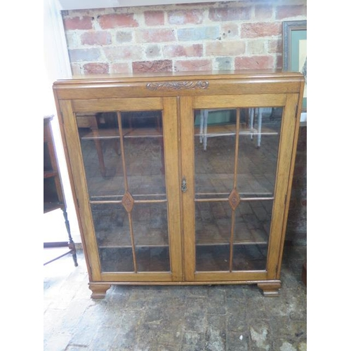 89 - A light oak two door display cabinet with adjustable shelving, 122cm tall x 107cm x 29cm, in good co...