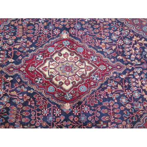 202 - A hand woven woollen Sarouk rug with a blue field, 2m x 1.31m, in good condition