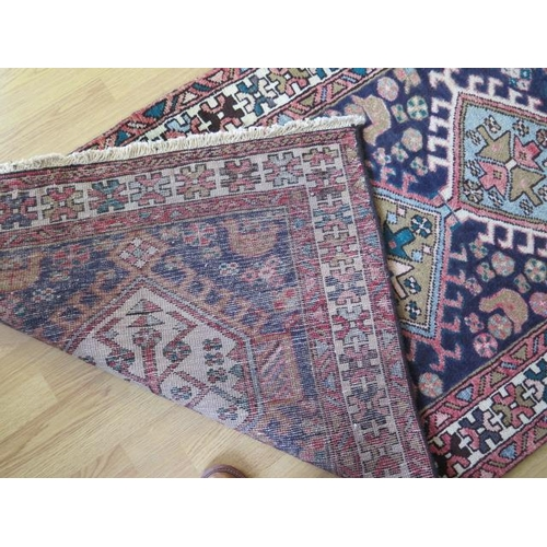 208 - A hand woven woollen Heriz runner with a blue field, 3.28m x 1.00m, in good condition