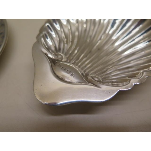519 - A silver shell dish and a continental white metal cup and saucer, total weight approx 4.7 troy oz, g...
