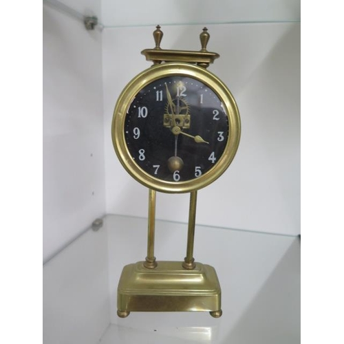 152 - A brass twin pillar drum gravity clock, 26cm tall, ticks but stops