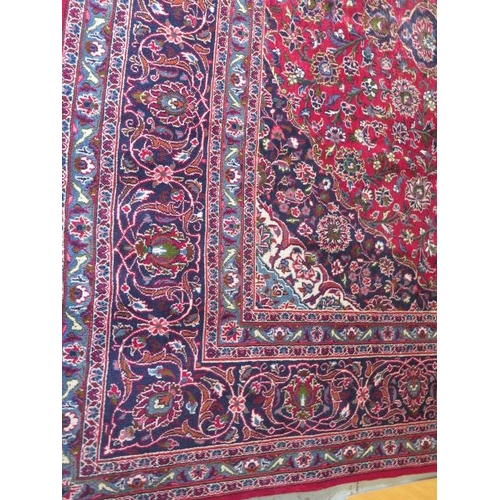 201 - A hand woven large red ground Persian woollen Kashan carpet, 405cm x 284cm, some wear consistent wit...