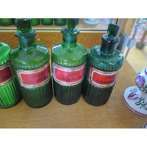 295 - A coloured group of 14 chemist bottles, 3 glass measures and 3 ceramic jars, all but one of the gree...