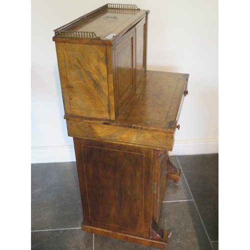 50 - A good Victorian walnut writing desk with a two door brass galleried top with fitted interior above ...
