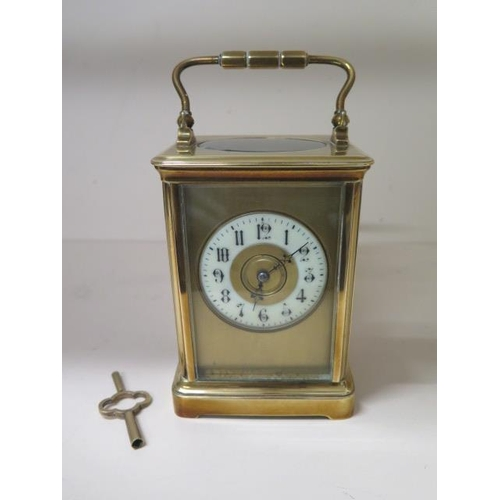 152 - A brass carriage clock striking on a gong, 18cm tall with handle up, running order, one glass panel ...