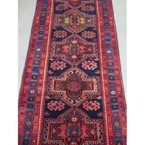 203 - A blue and red ground hand woven runner with a cross door design, some wear but colours bright, 305c...