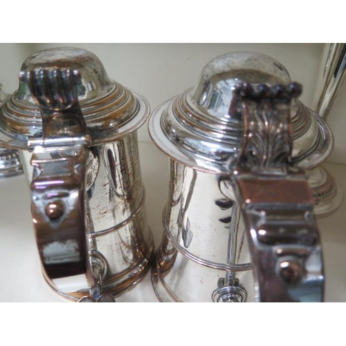 506 - A near pair of Sheffield plate lidded tankards, 20cm tall, some wear to plate, one has a wooden inse...