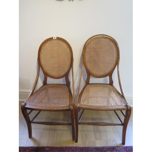 52 - A pair of walnut side chairs with caned seats and backs, one seat needs recaning otherwise good