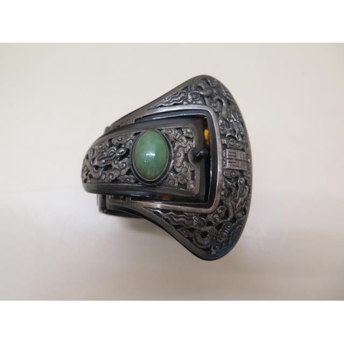 613 - A Chinese folding tortoiseshell and white metal bangle set with a green jade cabouchon, 7cm wide whe...