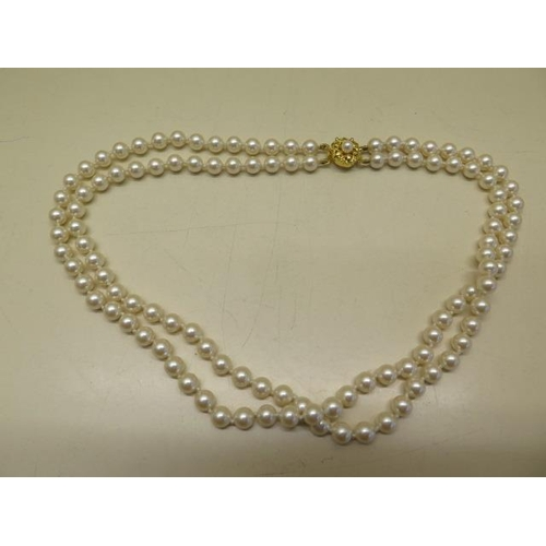 616 - A double row of simulated pearls, approx size 6mm, all strung and knotted on thread and complete wit...