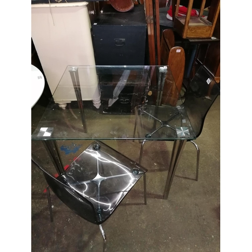 24 - Modernist glass dining table and two chairs with chrome frame and clear perspex seats; ht 74cm, 85 x...