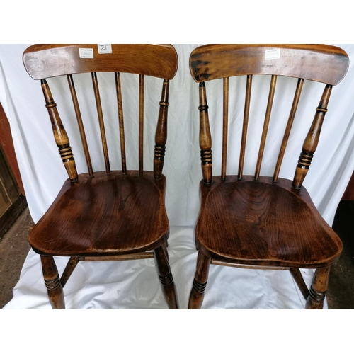 21 - A pair of antique stick-backed kitchen chairs each with elm saddle seats, raised on turned supports ...