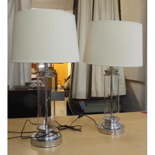 42 - ANDREW MARTIN HAMILTON TABLE LAMPS, a pair, each with a glass column, a cream shade and a circular p...