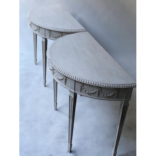 CONSOLE TABLES, a pair, George III design, Robert Adam style demi lune grey painted with ribbon swag frieze and square tapering supports, 99cm W x 50cm D x 77cm H. (2)