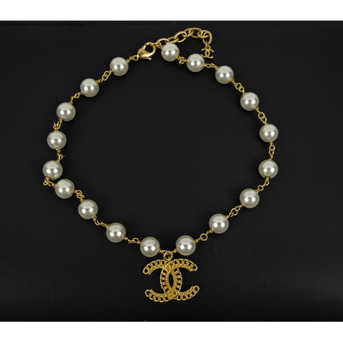 CHANEL NECKLACE, pearl and classic CC logo design.