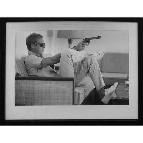 14 - AFTER JOHN DOWNING, Steve McQueen with gun, framed and glazed, 73cm x 53.5cm.
