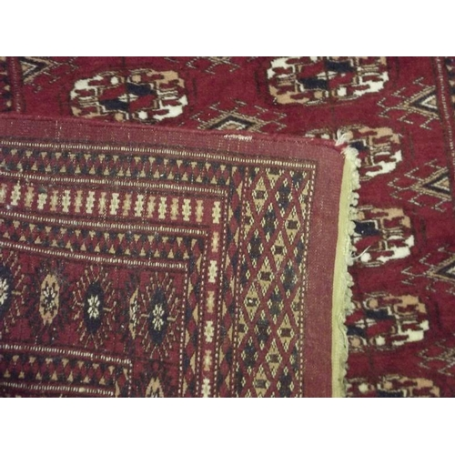 13 - Persian red ground rug, medallions to the centre with a multiple geometric border, 58 in. x 38 in....