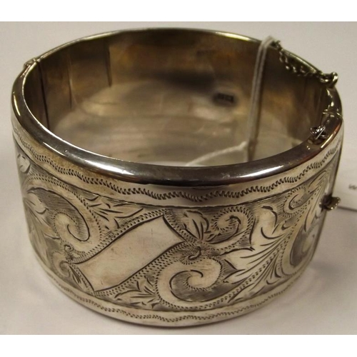 2 - Broad silver bangle with scroll engraved decoration to one half, Birmingham 1963, 1.8 oz....