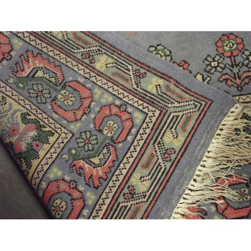 25 - Persian blue ground wool rug with floral border....