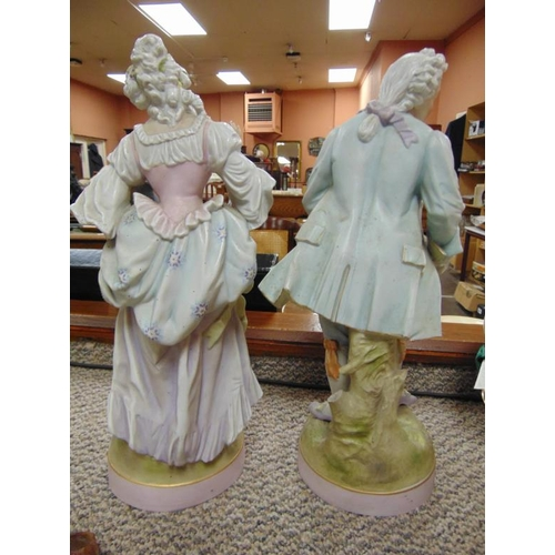 19 - Pair of continental porcelain figures of a gentleman and lady, 15.5in. high.