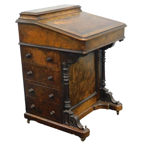 11 - A Victorian figured walnut Davenport, the hinged top enclosing a fitted interior, the slope with a l...