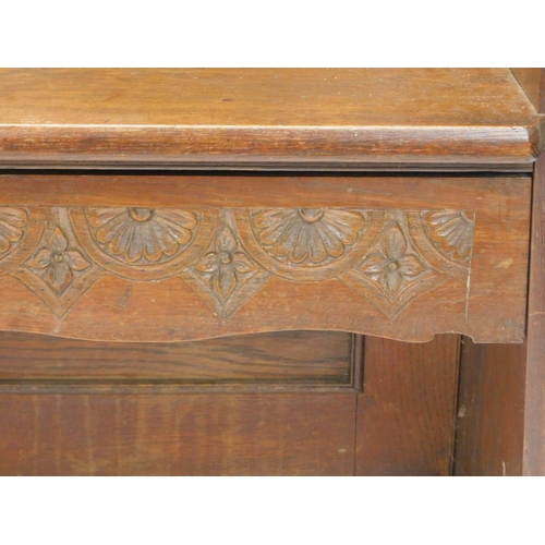 30 - An early 20thC oak settle with a carved panelled back shaped sides and double seat, 107cm W....
