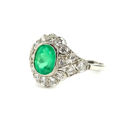 51 - An emerald and diamond platinum dress ring, with central oval cut emerald approx 1.08cts, surrounded...