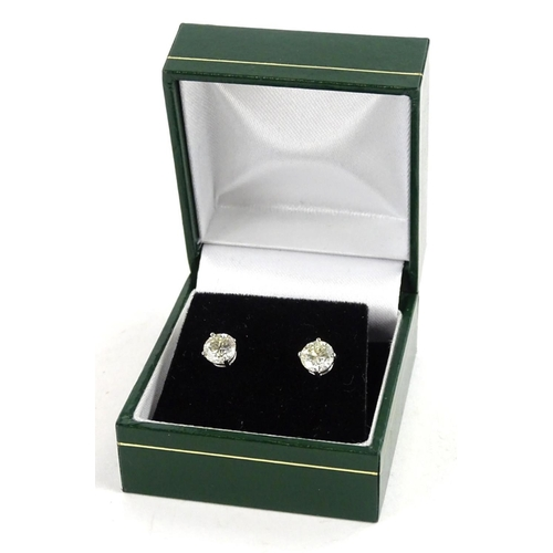 57 - A pair of 18ct white gold diamond earrings, with round brilliant cut diamonds, each in claw setting,...