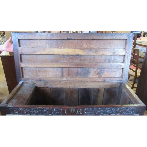 11 - An antique oak mule chest, with rising lid, the front carved with flowers and leaves, fitted with tw...