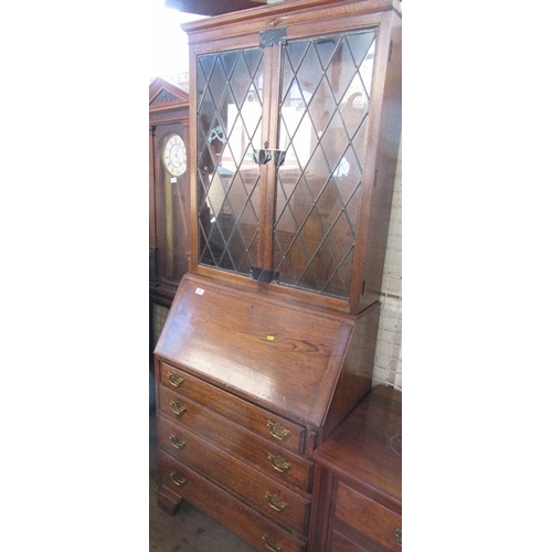 14 - A 20th century oak bureau bookcase, with lead glazed doors to the upper section, height 78ins x widt...