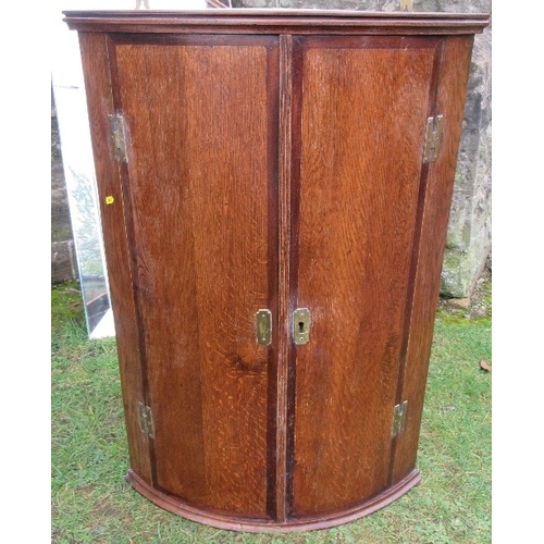 20 - An antique oak corner cupboard, with mahogany banding, the barrel front opening to reveal shelves, h...