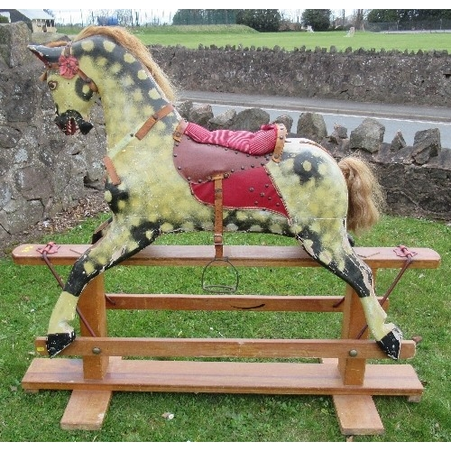 21 - A carved and painted rocking horse, dapple grey horse, with leather and upholstered saddle, on a pin...