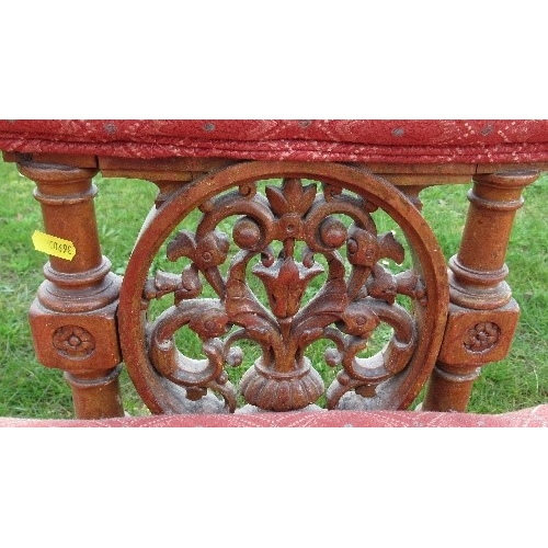 22A - A Victorian show wood settee, with upholstered shaped top rail, having carved and turned supports to...