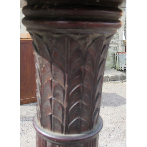 25 - A mahogany torchere, with carved column, raised on three outswept supports, height 60ins