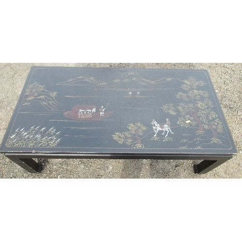 34 - A 20th century oriental style black lacquer coffee table, of rectangular form, decorated with figure...